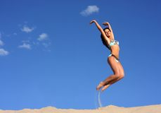 Jumping happy girl. Emotional jumping happy girl on the beach Royalty Free Stock Photography
