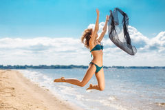 Jumping happy girl on the beach, fit sporty healthy sexy body in bikini Stock Images