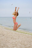 Jumping happy girl on the beach, fit sporty healthy sexy body in bikini Stock Image