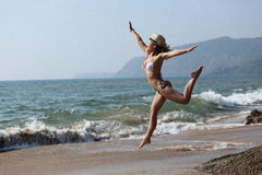 Jumping happy girl on the beach, fit sporty healthy sexy body in bikini. Royalty Free Stock Image