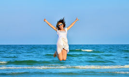 Jumping happy girl on the beach Stock Image