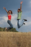 Jumping happy young couple stock photos