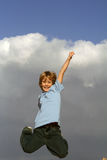 Jumping high. Boy jumping triumphantly in air Stock Image