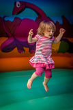 Jumping high. Cute little girl jumping inside the inflatable bouncy castle Stock Photo