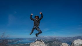 Jumping high from the rock. Tourist with a hat jumping high from the large boulder rock in Lovcen National Park, Montenegro stock photo