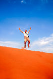 Jumping high on the sand dunes. Tourist jumping in the air at the stunning sand dunes of Sahara desert, Merzouga, Morocco stock photography