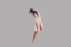 Jumping so high. Studio shot of attractive young woman hovering in air Stock Photography