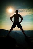 Jumping hiker in black pants celebrate triumph between two rocky peaks. Wonderful sunny daybreak. royalty free stock photos
