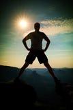 Jumping hiker in black pants celebrate triumph between two rocky peaks. Wonderful sunny daybreak. Royalty Free Stock Photos
