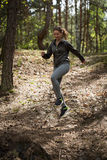 Jumping of the hillock. Active running girl jumping of the hillock in the woods stock photos