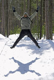 Jumping jack. Man jumping in woods with shadow on snow Royalty Free Stock Photos