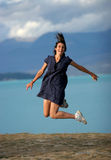 Jumping for joy. Girl jumping high against a lake stock photography