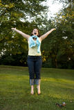 Jumping for Joy. Young brunette woman jumps for joy, her arms out stretched, on a tree lined grass lawn royalty free stock photos