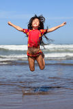 Jumping for joy. Little girl jumping in the ocean Stock Photos