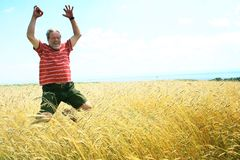 Jumping with joy. A senior man in a red striped t-shirt jumping in a meadow, expressing joy/victory Stock Photo