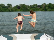 Jumping for Joy. My daughter and her friend jumping for joy off our boat on the 1st day off for the summer Stock Photography