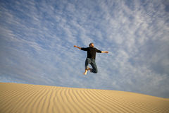 Jumping With Joy. A man jumping with joy off a sand dune Stock Image