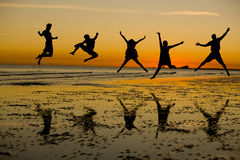 Jumping With Joy. Friends jumping on the beach Royalty Free Stock Photo