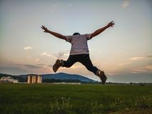 Jumping in Joy. A boy jumping in joy having fun in the evening stock photography