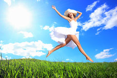 Jumping for Joy on a Grass Hill Stock Photo