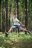 Jumping for joy in the park. Young man jumping for joy outdoor in the park Stock Photo