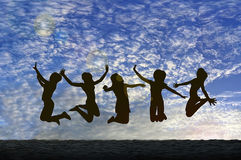 Girls jumping with Joy on the beach silhouetted against a cloudy sky Stock Images