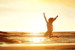 Jumping for joy. Silhouette portrait of young woman jumping for joy at beach during sunset Royalty Free Stock Photos