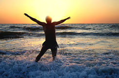 Jumping for joy in the sunset on the ocean Stock Photography