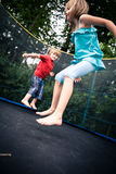 Jumping kids. Jupming kids on the trampoline in the garden stock image