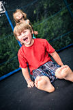 Jumping kids. Jupming kids on the trampoline in the garden royalty free stock photos