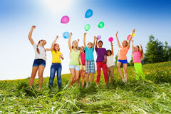 Jumping kids with flying balloons in summer. Jumping kids with flying balloons in the air in green field in summer Royalty Free Stock Photo