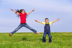 Jumping kids on green field Stock Photo