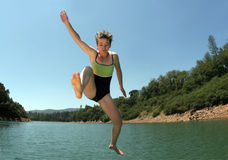 Jumping in the lake. Young woman jumping in the lake Royalty Free Stock Photos