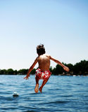 Jumping in the Lake. A little boy jumping into the water stock photography