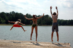 Jumping into lake. Three children jump off dock into lake stock photo