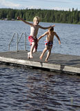 Jumping in a lake. Two happy boys jumping in a lake from a bridge Royalty Free Stock Photography