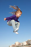 Jumping little girl. Cute girl jumping high in the blue sky Royalty Free Stock Photography