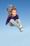 Jumping little girl. Little girl jumping high in the sky Stock Images