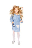 Jumping little girl. In a blue dress with flying curls Royalty Free Stock Image