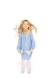 Jumping little girl. In a blue dress with flying curls Royalty Free Stock Photography