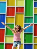 Jumping little girl on colorful mosaic background.