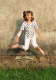 Jumping little girl Stock Images