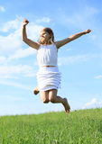 Jumping little girl. Cute little kid - blond girl in white skirt an t-shirt jumping on green grass of meadow Stock Images