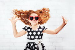 Jumping little girl with flying hair. In a fashionable dress Stock Images