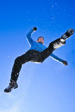 Jumping man. Man in sportswear jumping in the snow on a beautiful blue background Royalty Free Stock Photos