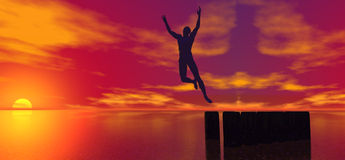 Jumping man. Silhouette of joyful man jumping with raised arms near sea at sunset Stock Photography