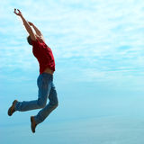 Jumping  man. Against sea with blue sky and clouds Stock Image