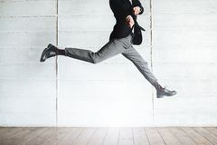 Jumping man in black costume in the office stock photos