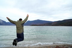 Jumping man with lake Stock Image