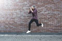 Jumping man with retro photo camera Fashion Travel Lifestyle outdoor while standing against brick wall background royalty free stock image